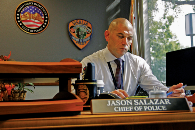 Visalia Chief of Police Jason Salazar looks over paperwork in his office after discussing the merits of the HOPE team. Salazar says calls in regards to homelessness, the most public face of mental illness is Visalia, grew by 900 percent between 2007 and 2017. (Photo via Paul Myers)