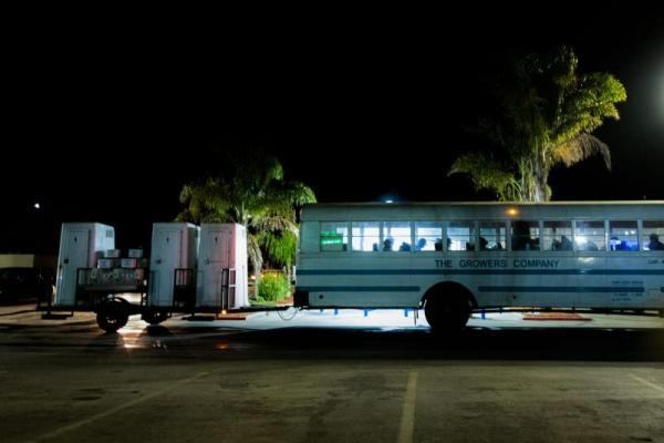 Hundreds of farmworkers gather at 4:30 a.m. every day during the seasonal harvest to board a labor bus that also hauls sanitary stations. The workers are in the fields by 6 a.m. (Sebastian Hidalgo/The Salinas Californian)