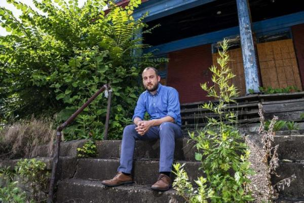 Artist Nathan Van Patter sits on the steps of an abandoned home, June 26 on Middle Street in North Braddock.