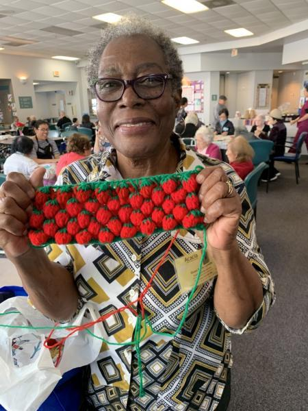 Lynette Quan Soon, 76, is a mother of seven. She proudly shows her crochet strawberries and other crafts that she makes. (Photo by Michelle Faust Raghavan/LAist)