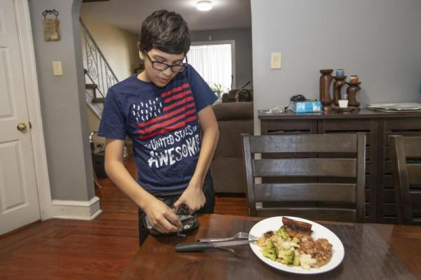 MICHAEL BRYANT / STAFF PHOTOGRAPHER David Garcia, 12, pricks his finger in order to take a reading of his blood sugar levels before he sits down to eat his dinner.