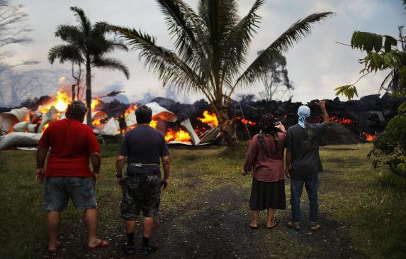 Community members watch as a home is destroyed by lava from a Kilauea volcano fissure in Leilani Estates, on Hawaii's Big Island