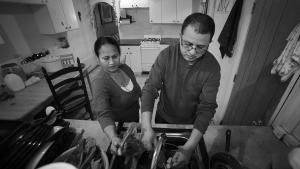 Tek Nepal (right) washes spinach at his Mount Oliver home with his wife Radhika Nepal.