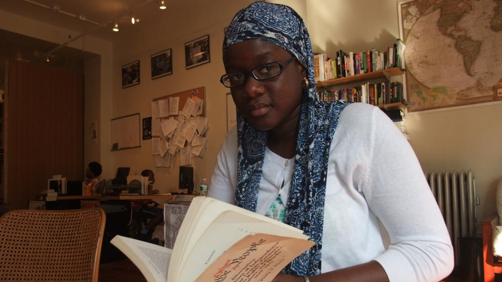 Fanta Fofana reads a book in the library.