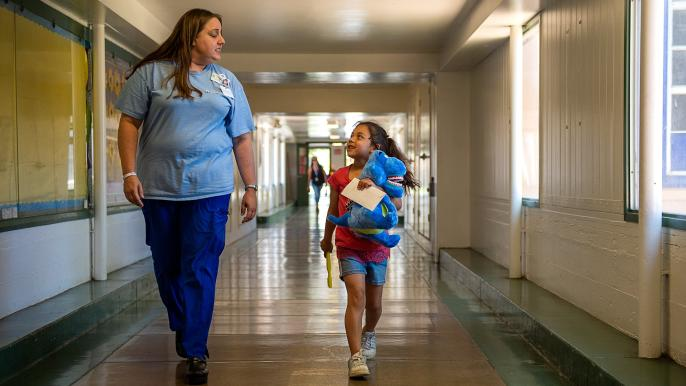 First grader Stephanie Rojas, 7, walks back to her class with dental coordinator Gizelle Jacobs after a dental visit
