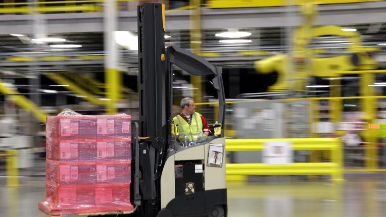 A forklift operator moves a pallet of goods at a warehouse, prepping for delivery. Photog: Ted Warren/AP