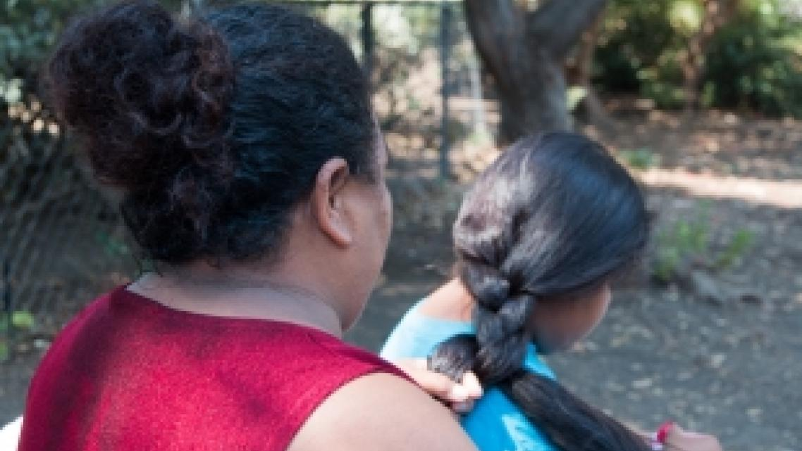 Victoria braids her daughter's hair after taking a shower at Hope's Corner. Photo by Ana Sofia Amieva-Wang