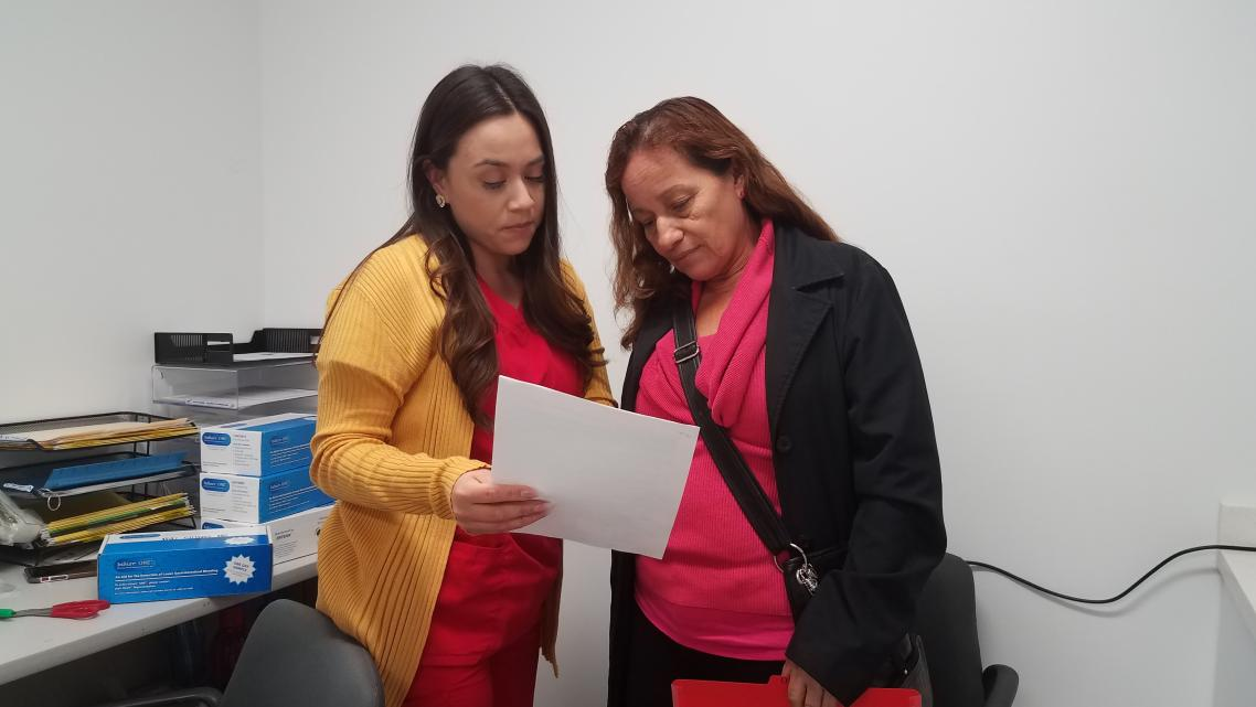 Medical assistant Deisy Hernandez discusses an upcoming appointment with patient Caya Mendoza, 62, inside Clinica Romero in Boy