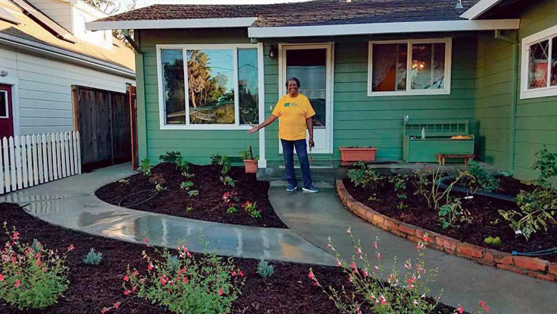 Carrie Whitley shows off a new garden in front of her Santa Cruz home. Habitat for Humanity Monterey Bay helped add a 500-unit A