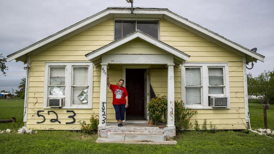 Sabine Wiegand, 55, leans against her abandoned home on 2nd Street in Bayside. Her mother, Patricia Wiegand; daughter; and grand
