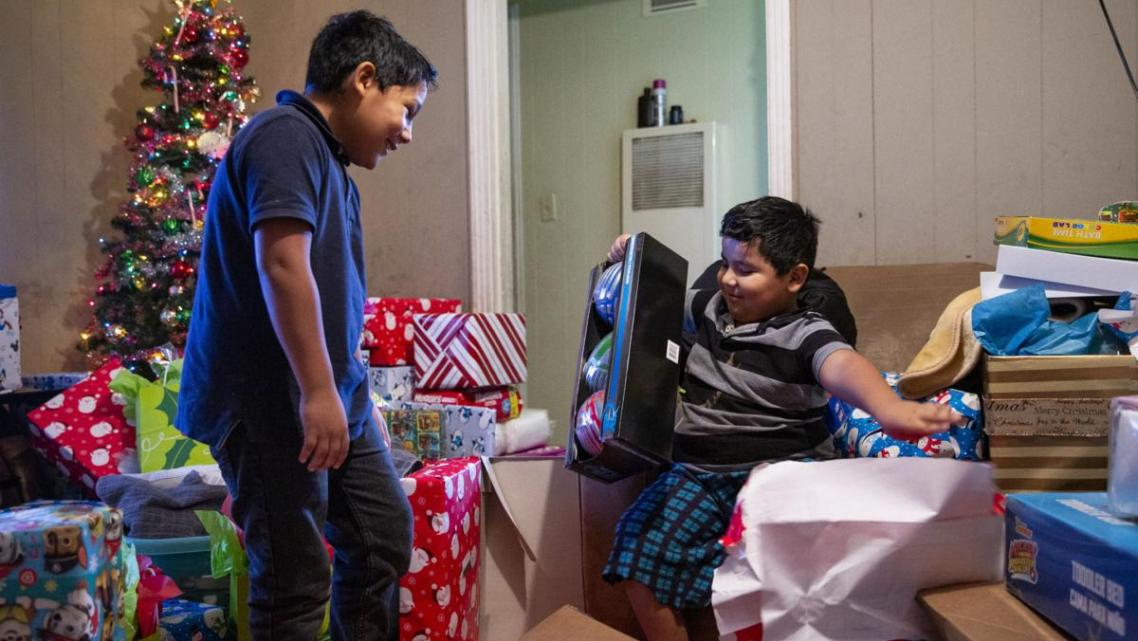 Fernando Martinez, 10, left, watches his brother, Jonathan Sanchez Jr., 6, open shiny sport balls after gifts were brought to th