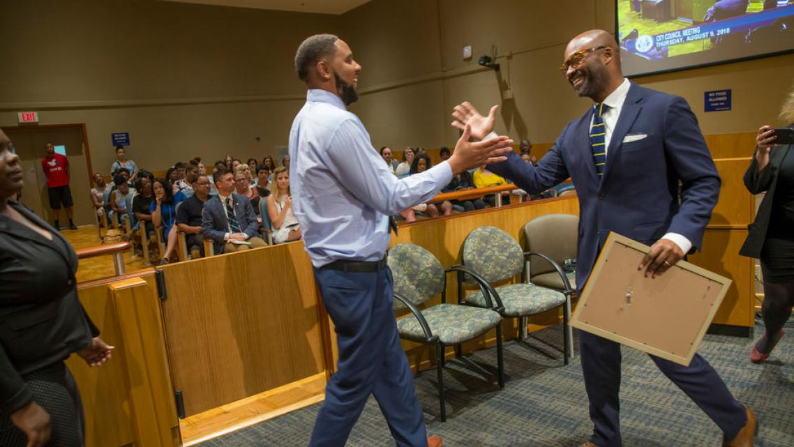 New Orleans Councilmember-at-Large Jason Rogers Williams, shakes hand of A. L. Davis Park Panthers head coach Shawn Scott