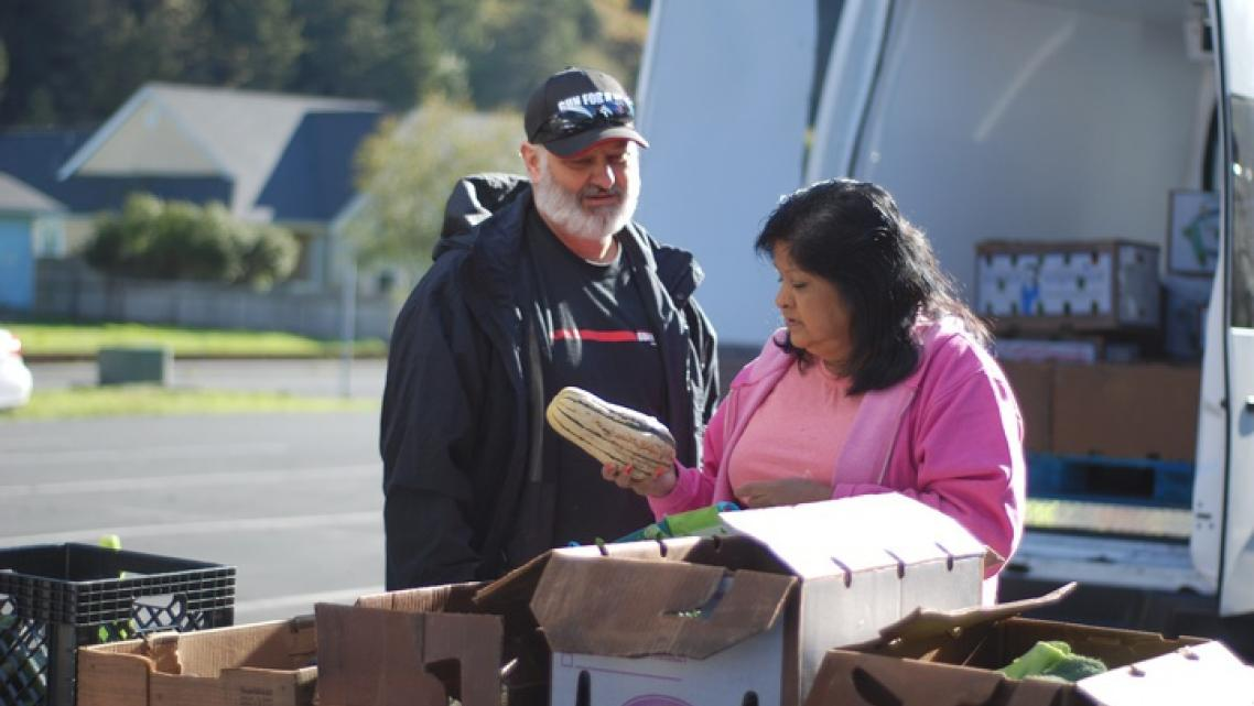 Shayne Britt and Roxie Reyes examine a delicata squash at an October visit of Food For People's Mobile Produce Pantry to Klamath