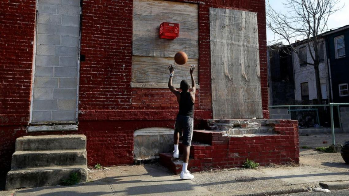 A boy shoots a basketball into a makeshift basket made from a milk crate and attached to a vacant row house in Baltimore, April 8, 2013. Patrick Semansky/AP Photo