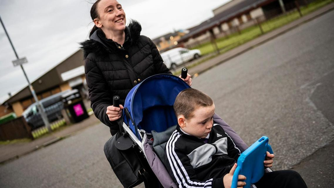 Leanne Quigley, of Possilpark, a neighborhood in Glasgow, pushes her son David Crichton, 7, back home.