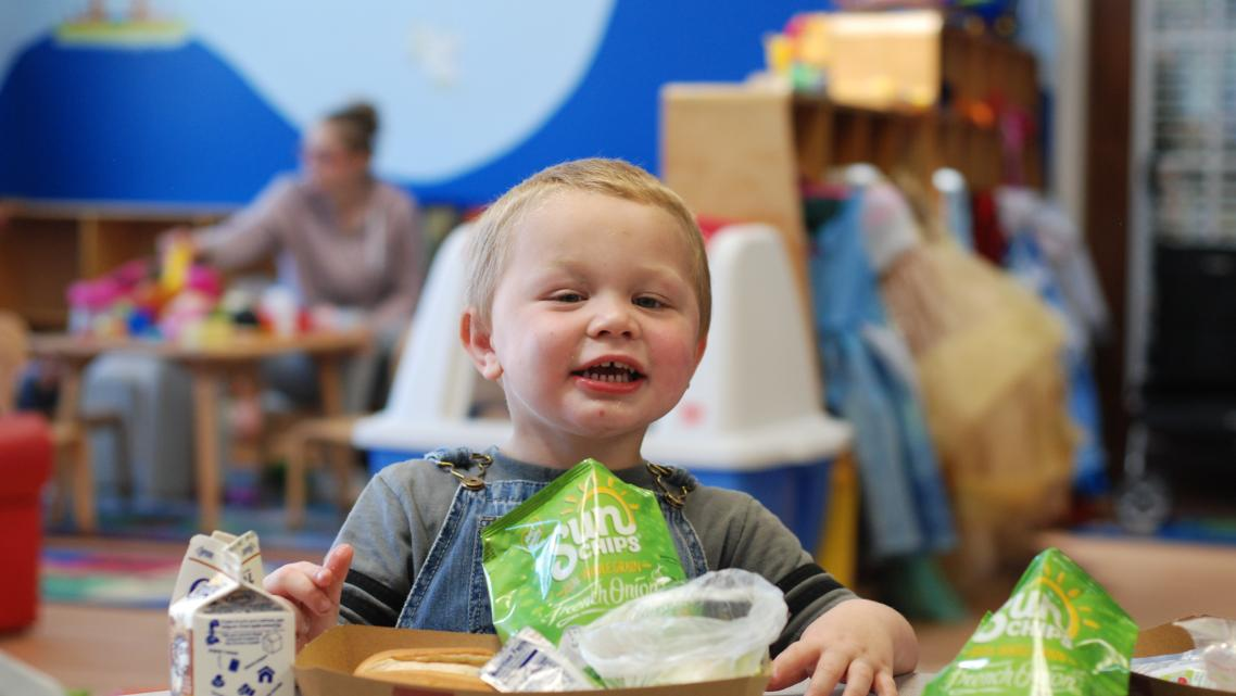 Two-year-old Jesse Bryson enjoys a bag of Sun Chips during the Seamless Summer Food program at the Family Resource Center of the