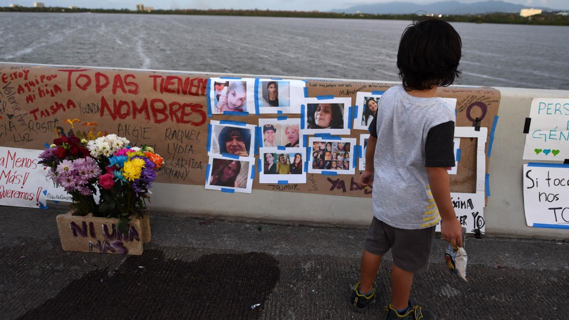 A child observes the photos of women victims of femicides that were placed as a tribute on the Teodoro Moscoso bridge.