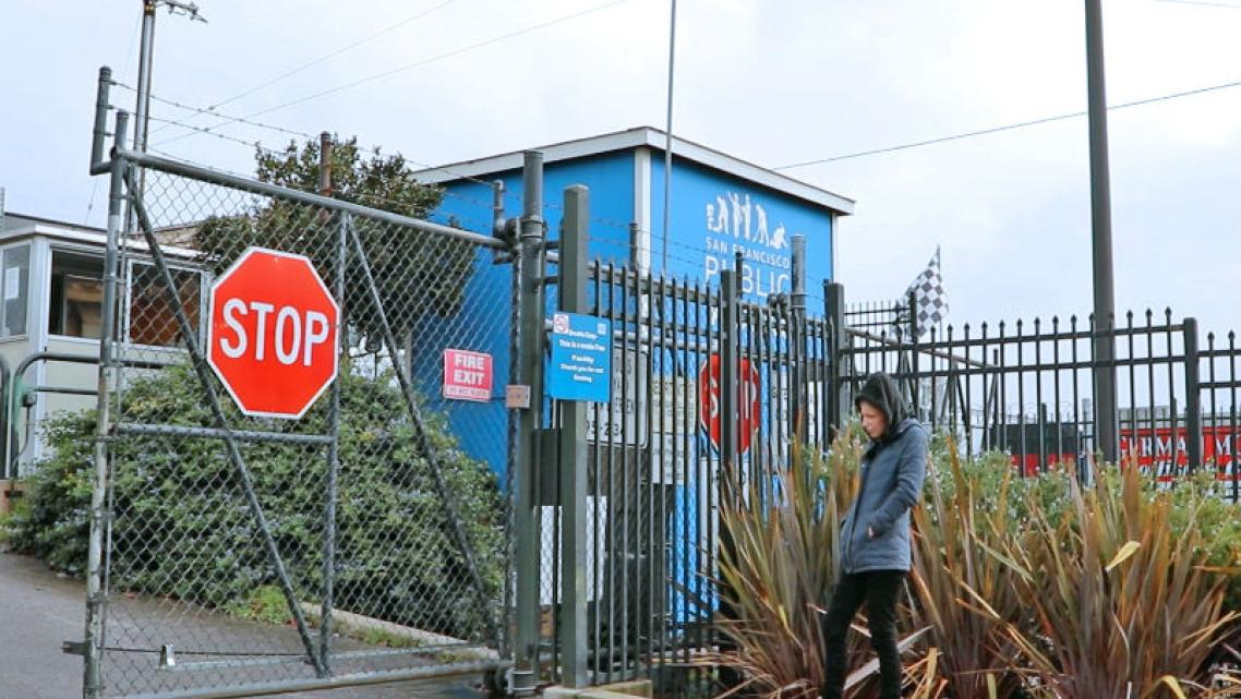 Heather Lee stands outside a closed gate at the Public Works yard after attempting to reclaim her belongings.