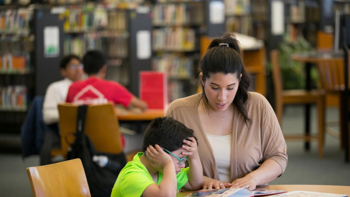Cristine Pagan helps her son Dean with reading homework at a local library. When Dean started first grade at Comly Elementary la