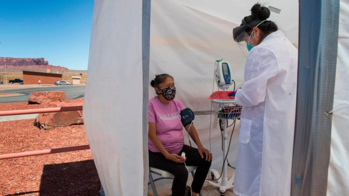 A nurse checks vitals on a Navajo woman complaining of virus symptoms at a COVID-19 testing center in Monument Valley, Arizona i