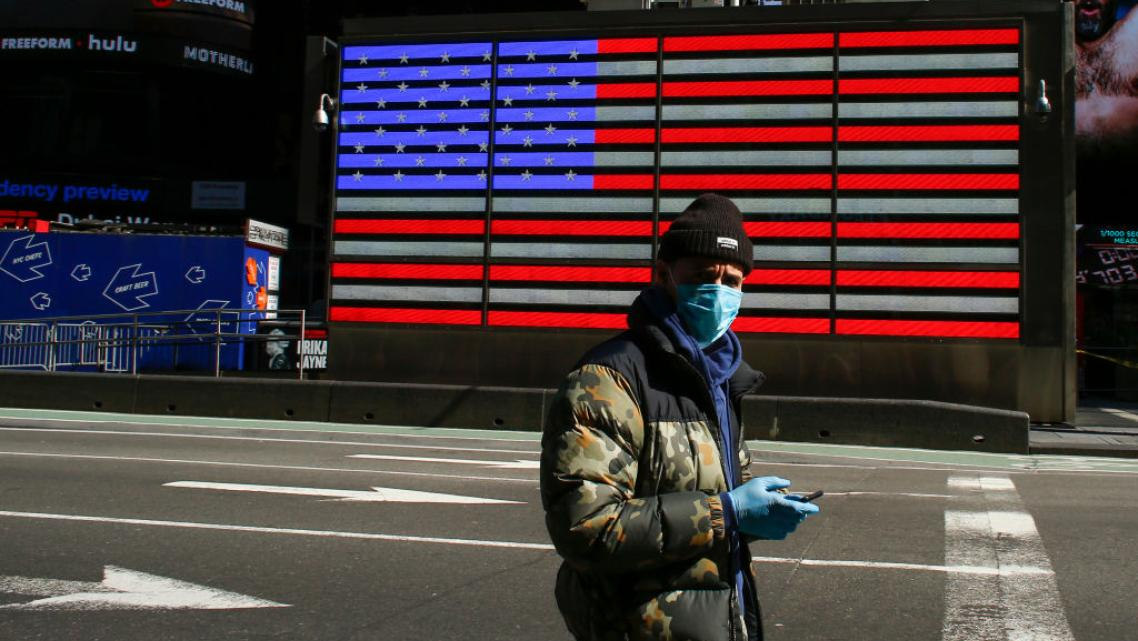 A man wears a face mask as he check his phone in Times Square in New York City.