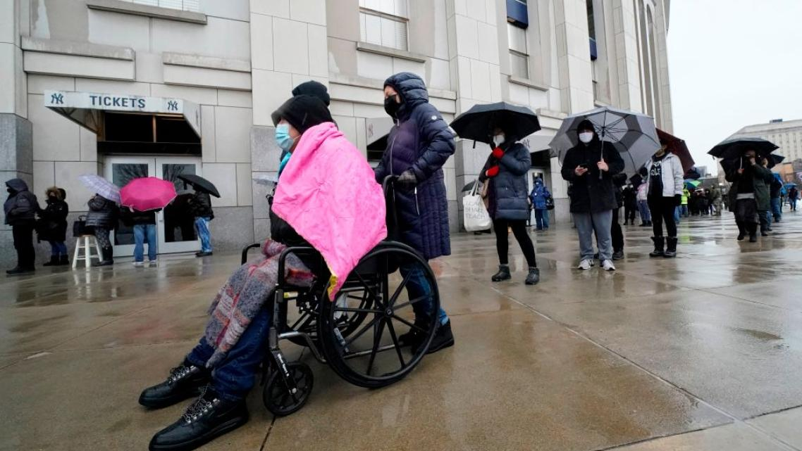 People line up in the rain outside the Yankee Stadium on February 5, 2021 in New York as the Stadium is turned into a mass Covid