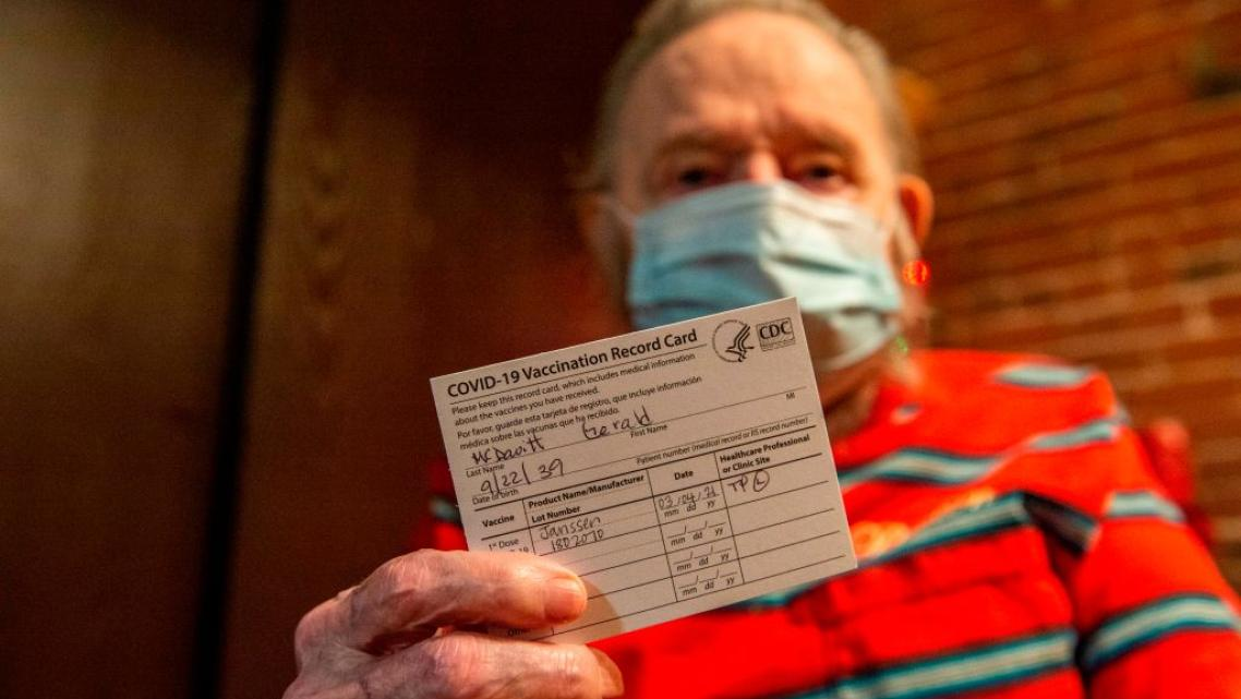 Gerald McDavitt, 81, a Veteran of the United States Army Corps of Engineers, holds his CDC vaccine card after being inoculated
