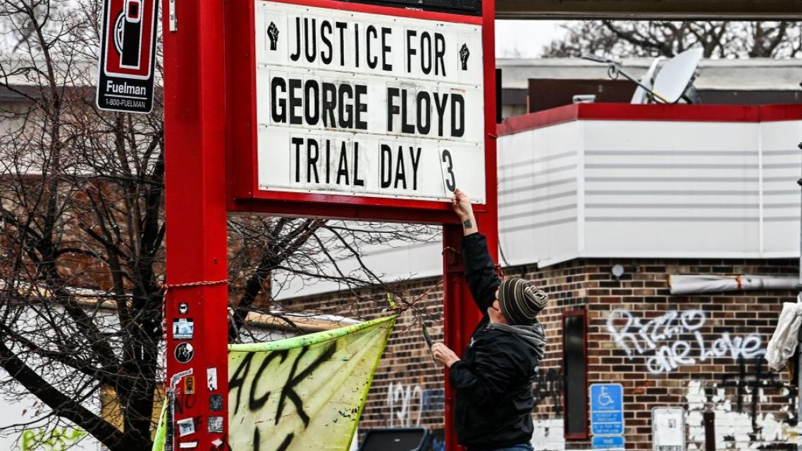 A man changes the number of a sign board at a makeshift memorial of George Floyd before the third day of jury selection begins i