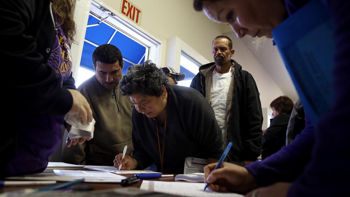 Attendees at a health insurance enrollment fair in Richmond, California fill out paperwork. (Photo by Justin Sullivan/Getty Imag