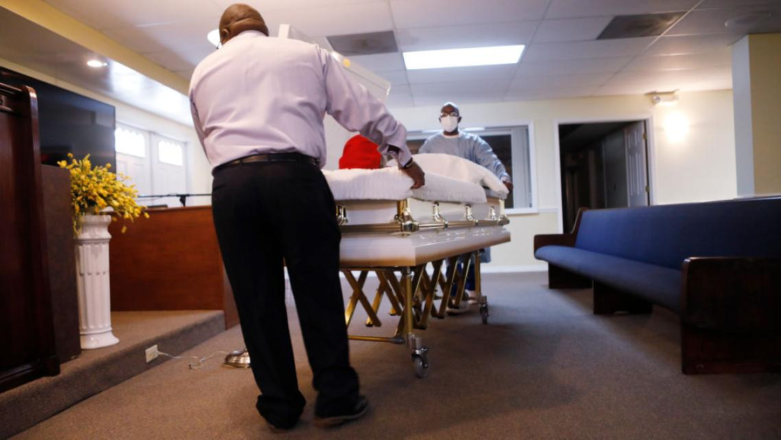A mortician assistant and embalmer prepare a funeral service for a man who died in August of COVID-19 at Ray Williams Funeral Ho