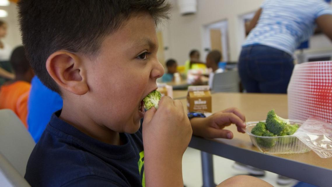 Six-year-old Jacob Portillo says he likes eating his broccoli at summer camp at Park View Recreation Center in Washington, D.C. The camp offers free lunches — funded by the USDA — to all participants and children in the community. For some, the meal fills a nutritional gap that's crucial during the summer months when kids are out of school. Photo by Margaret Myers/NewsHour