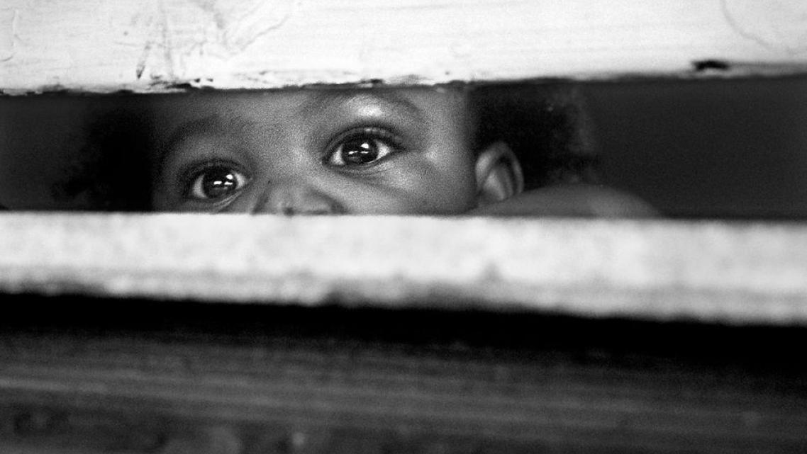 One-year-old CJ watches out the window as his older siblings, Skylar and Jaylen play in the front yard with his cousin.