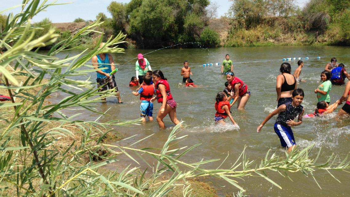 Kids play in the San Joaquin River. (Photo by Ezra David Romero/KVPR)