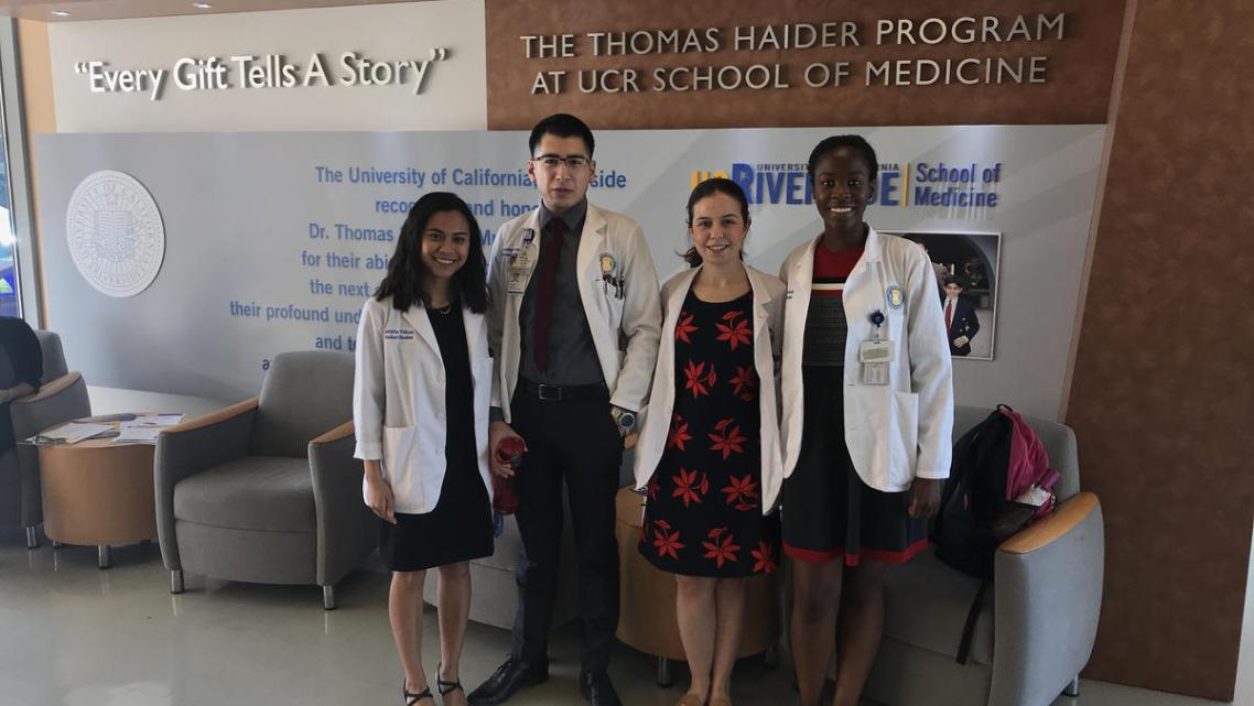 UCR medical students Jericha Viduya, Antonio Garcia, Monica Gutierrez, and Kleshie Baisie pose for a picture in their white coat