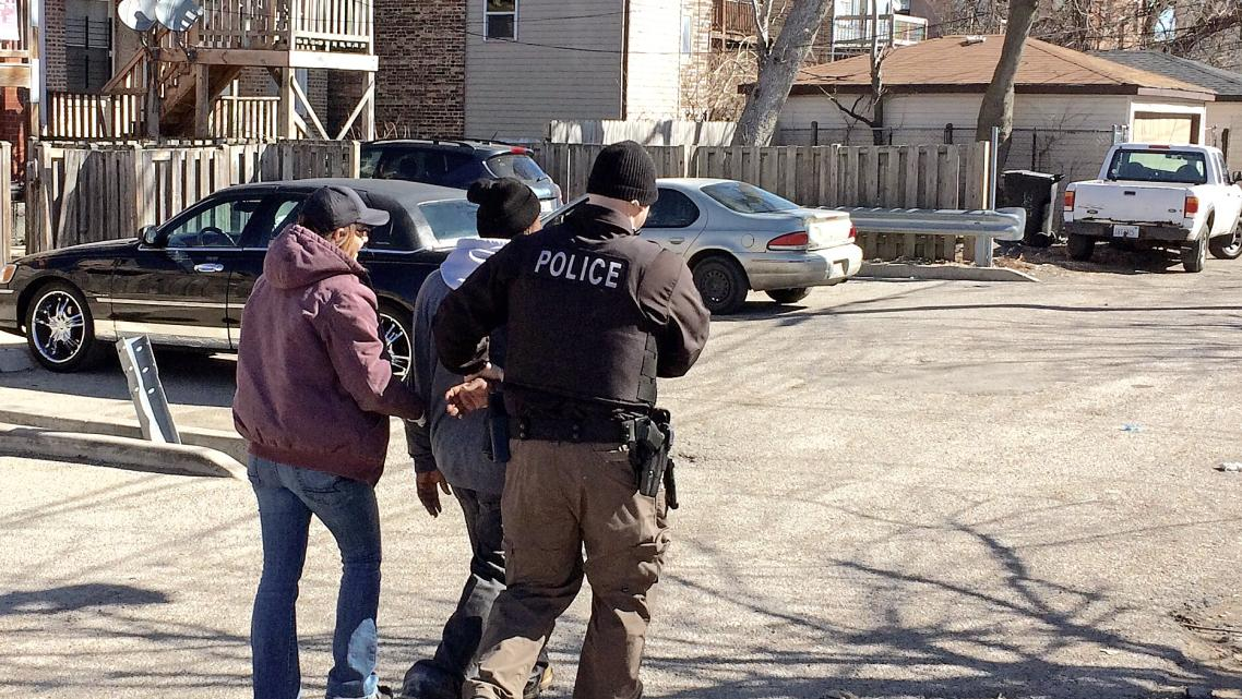Chicago police officers take a heroin buyer into custody on West Flournoy Street in Chicago.