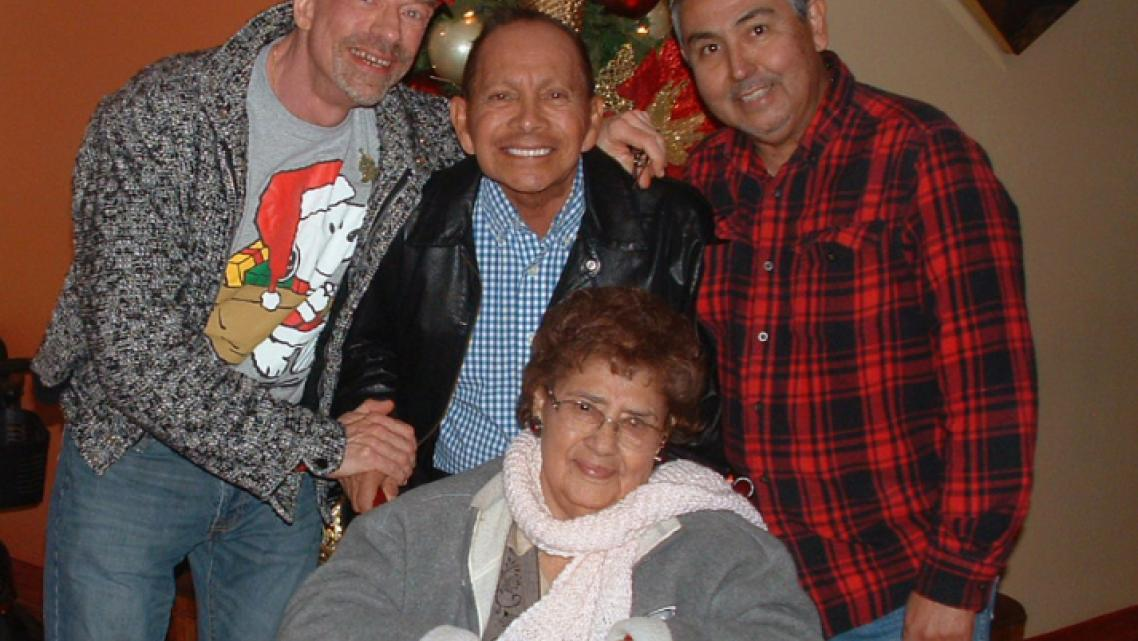 "Ed Harbur, Dave Gonzalez and Gustavo ""Sky"" Gonzalez with the Gonzalez's mother, Evangelina. Evangelina became infected with COVI"