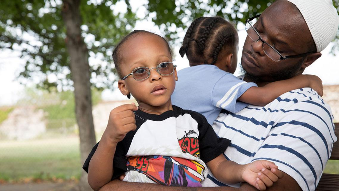 (Left to Right) Jihad and Murad sit with their dad, Andrew Irby, in the park. Irby worries about the future of his twin sons.