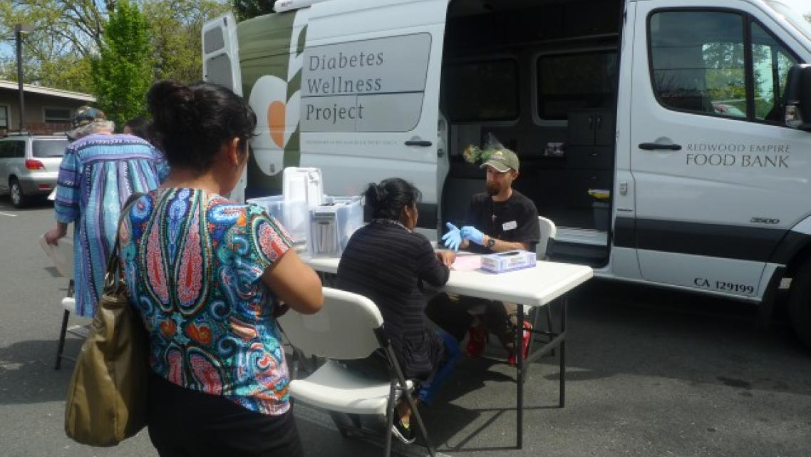 Morgan Smith, a registered nurse with the Redwood Empire Food Bank Diabetes Wellness Project, conducts free diabetes screenings once a month at the Graton Day Labor Center. The center serves as a conduit between its members — many of whom are undocumented — and health organizations around the region. (Lisa Morehouse/KQED)