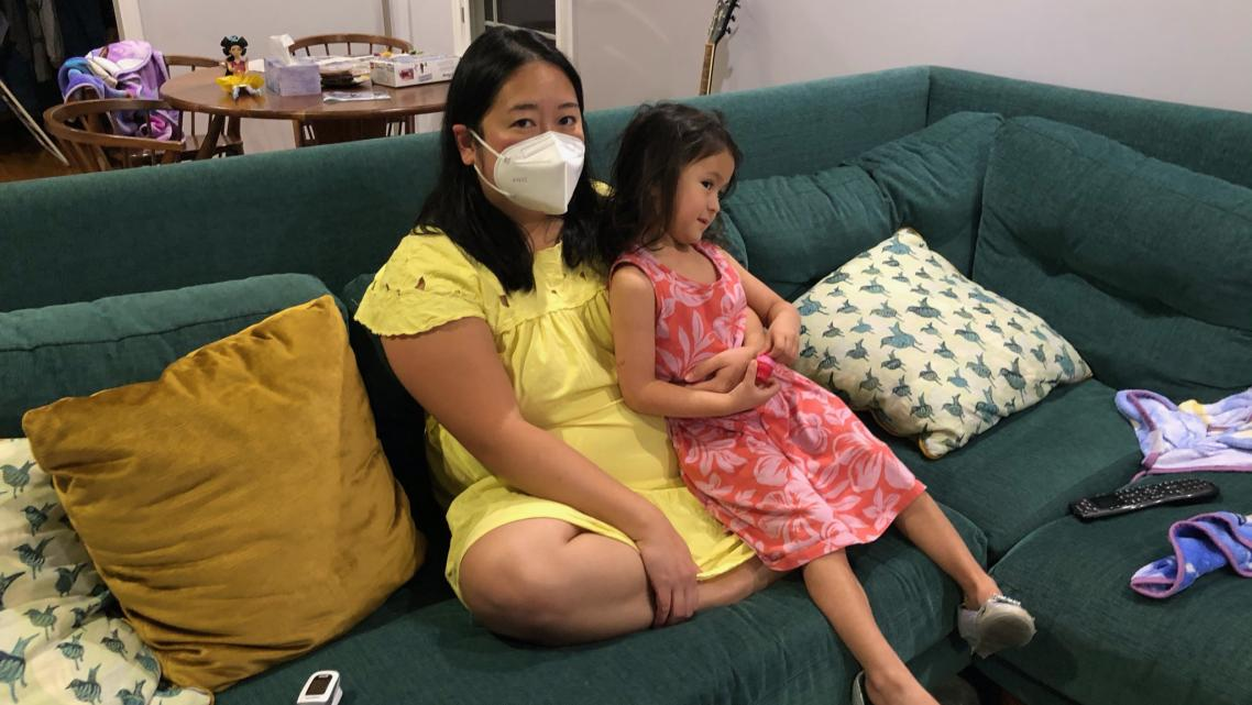 """Anna Almendrala takes a short break from her oxygen concentrator to watch TV with her daughter, Marigold """"Goldie"""" Ganz, three da"""