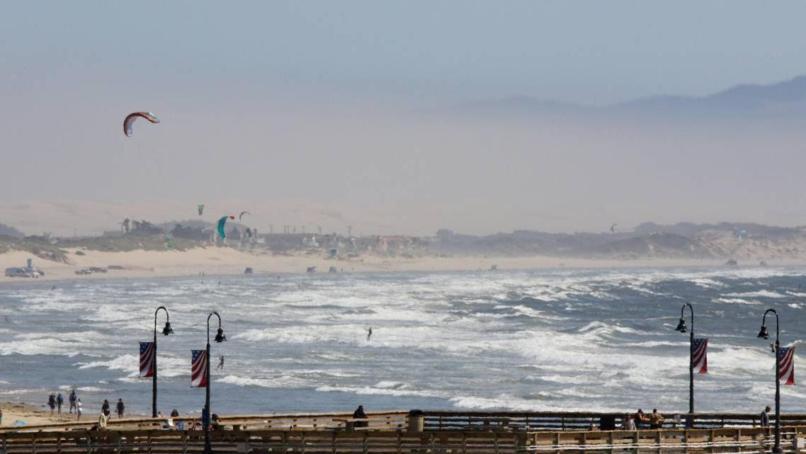 Wind brought out windsurfers south of Pismo Pier on August 21. It also contributed to a dusty haze obscuring the view.