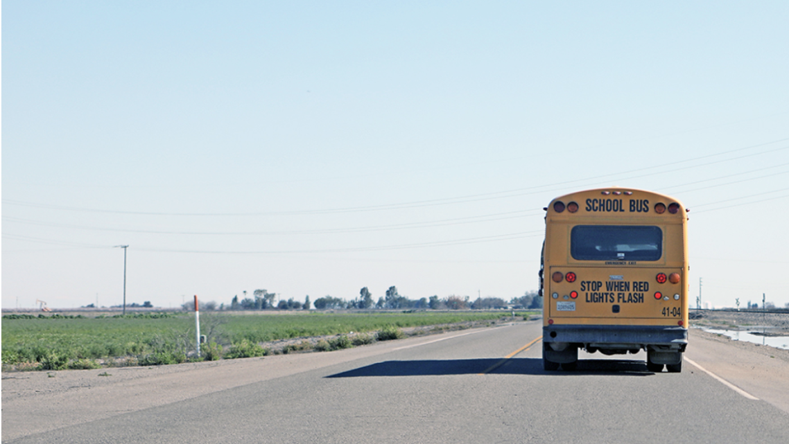 A rural school bus heads out to a campus to pick up students.