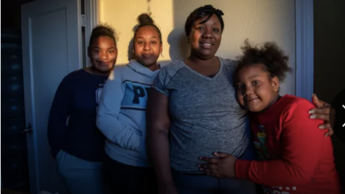 Tanya Harris and her daughters stand inside their restroom for a portrait on Feb 04