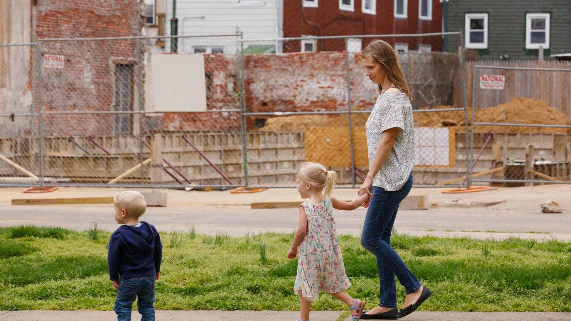 Jana Curtis and two of her children walk past one of many construction sites in their river ward neighborhood.