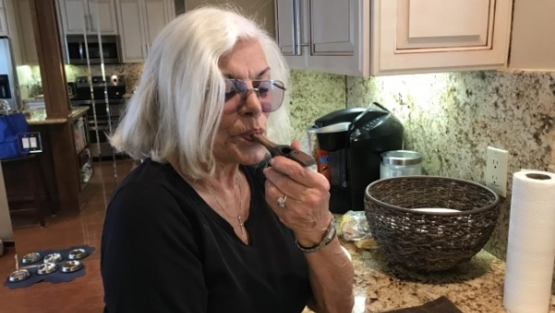 Linda Tisbo, a member of the Laguna Woods Medical Cannabis Collective, cleans out her pipe on April 11, 2018.