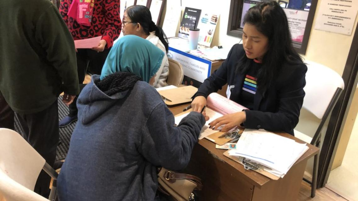 A health program director at the Cambodian Family, helps a client fill out paperwork. Many community organizations help bridge t