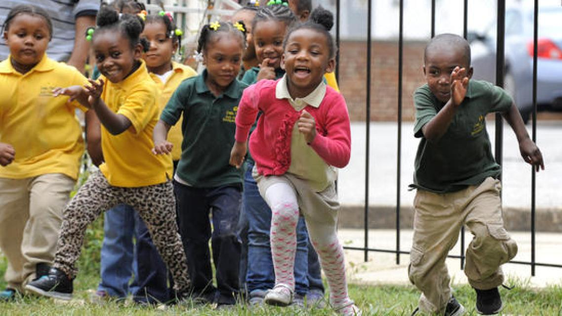 Students at Little Flowers Child Development Center laugh and play during a morning on the playground. Some of the children who attend the Baltimore school are exposed to violence in their neighborhood - an exposure scientists increasingly realize can cause health impacts. (Lloyd Fox, Baltimore Sun)