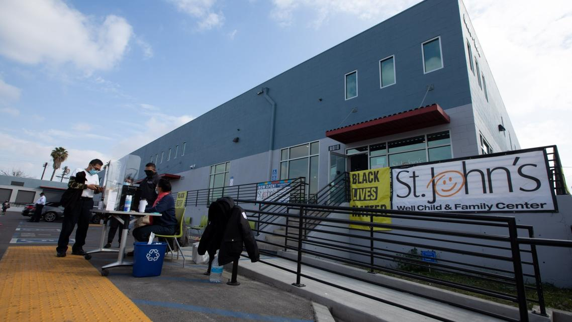 Patients arrive at the St. John's Well Child And Family Center to get inoculated with the Pfizer COVID-19 vaccine in South LA