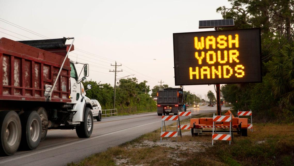A sign along Immokalee Road encourages people to wash their hands and stay six feet apart to limit the spread of coronavirus in