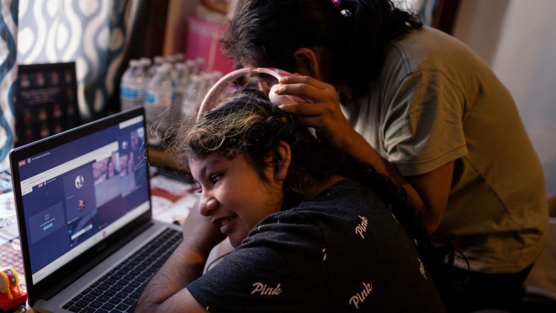Sarai Camarillo (right) shares headphones with her sister, Isamari Lucero, 13, as she learns remotely from their Little Village