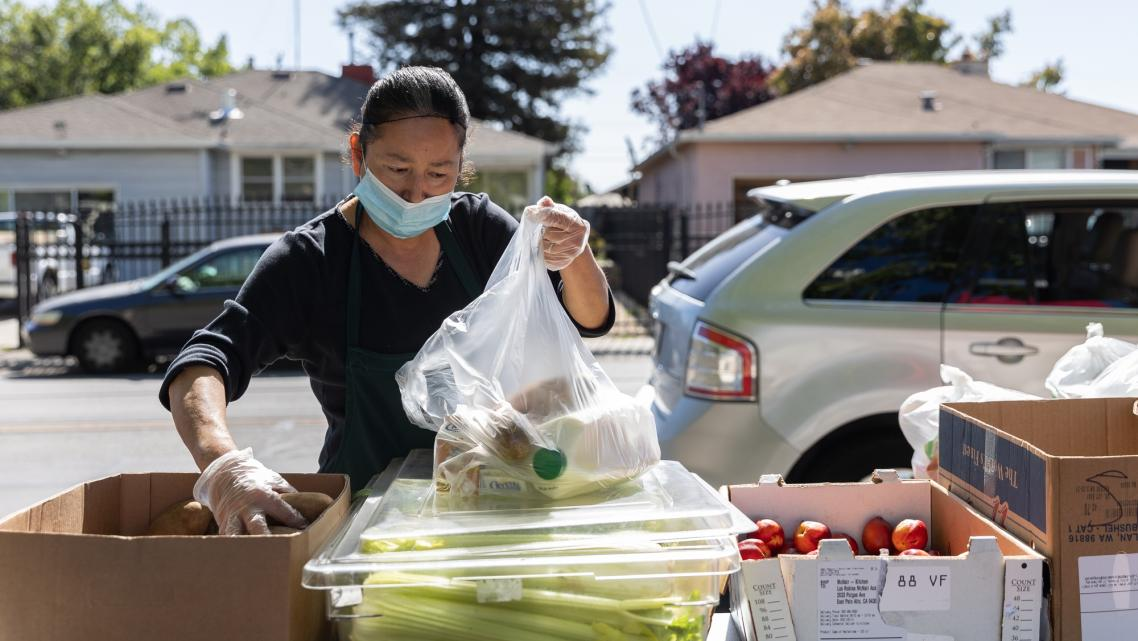 Norma Lazcano places potatoes in a bag at a food pick-up site at the Los Robles Ronald McNair Academy in East Palo Alto on May19
